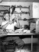Harold seated at work bench in his home jewelry shop.  Click on image to enlarge.